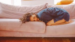 menina jovem deitada de buços imaginando como aliviar colica