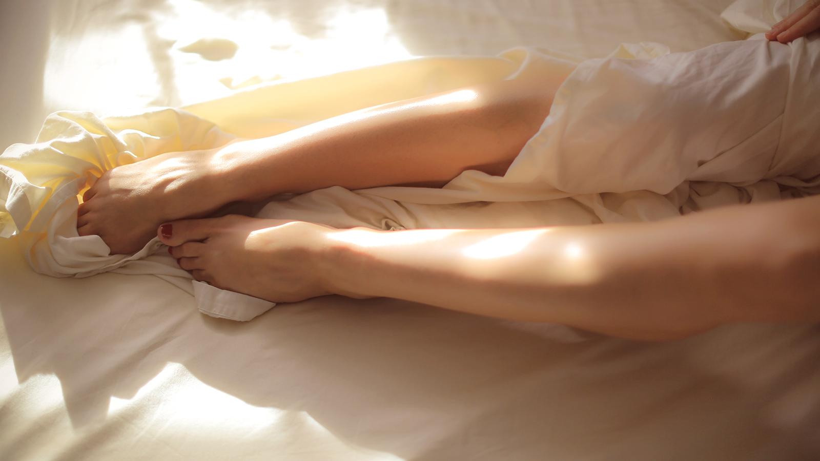 pernas femininas em uma cama representando prazer feminino