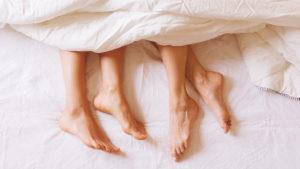 duas pessoas deitadas em uma cama com somente os pés aparecendo representando a primeira vez