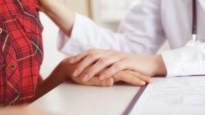 medica segurando a mao de uma jovem explicando o que é ginecologista