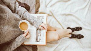 mulher jovem praticando autocuidado tomando café e lendo um livro