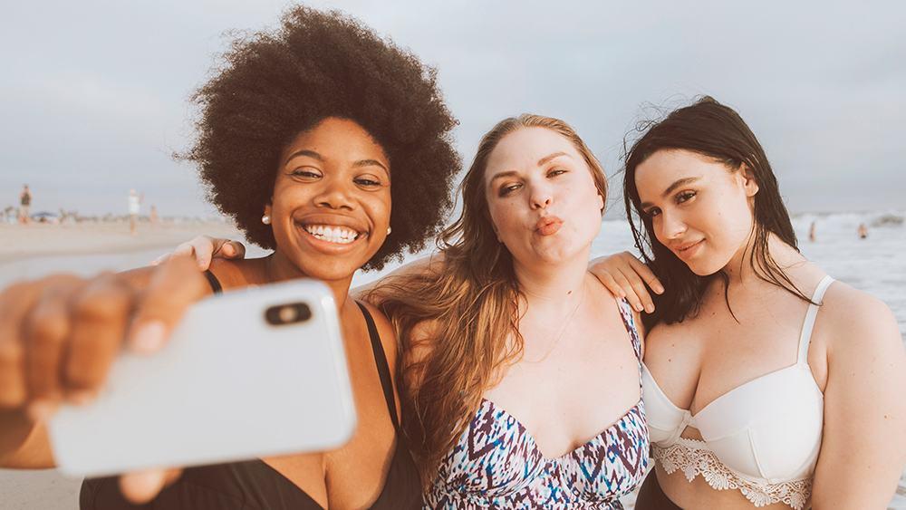 amigas jovens com autoestima tirando foto na praia