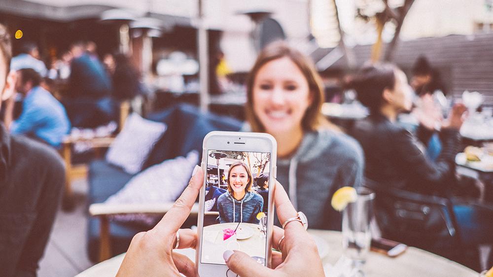 mulher usando iphone para tirar foto para instagram de sua amiga