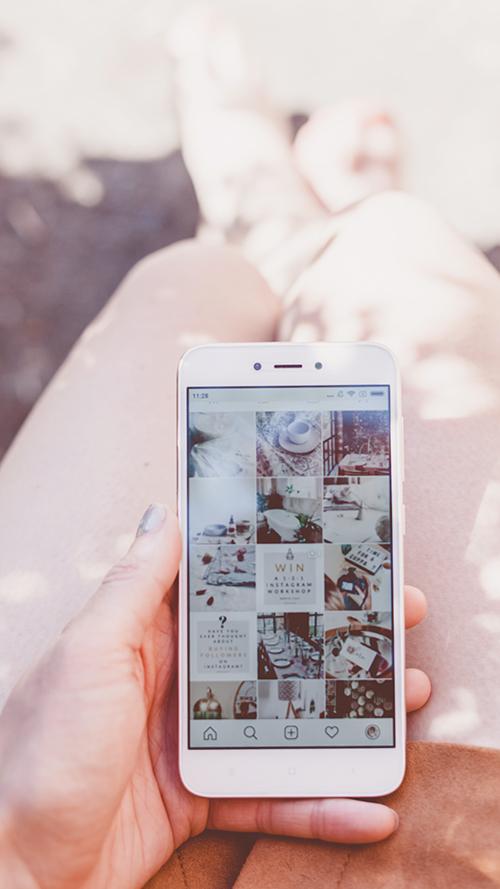 mãos fenininas usando um iphone para ver um feed organizado no instagram