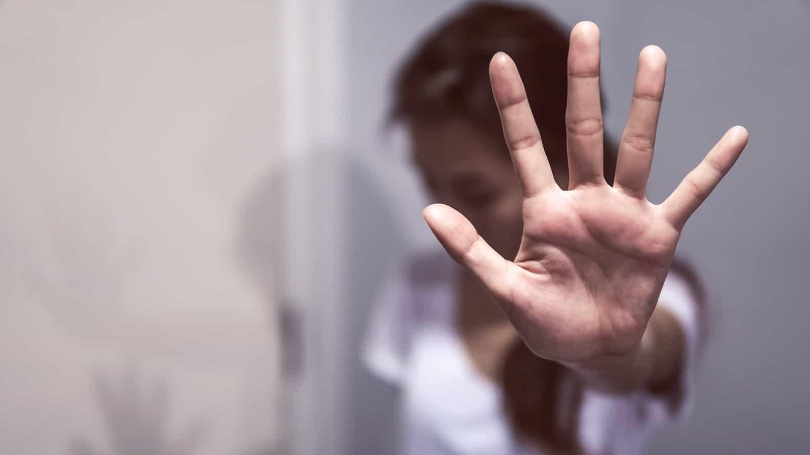 mulher jovem sofrendo um relacionamento abusivo com a mão no vidro