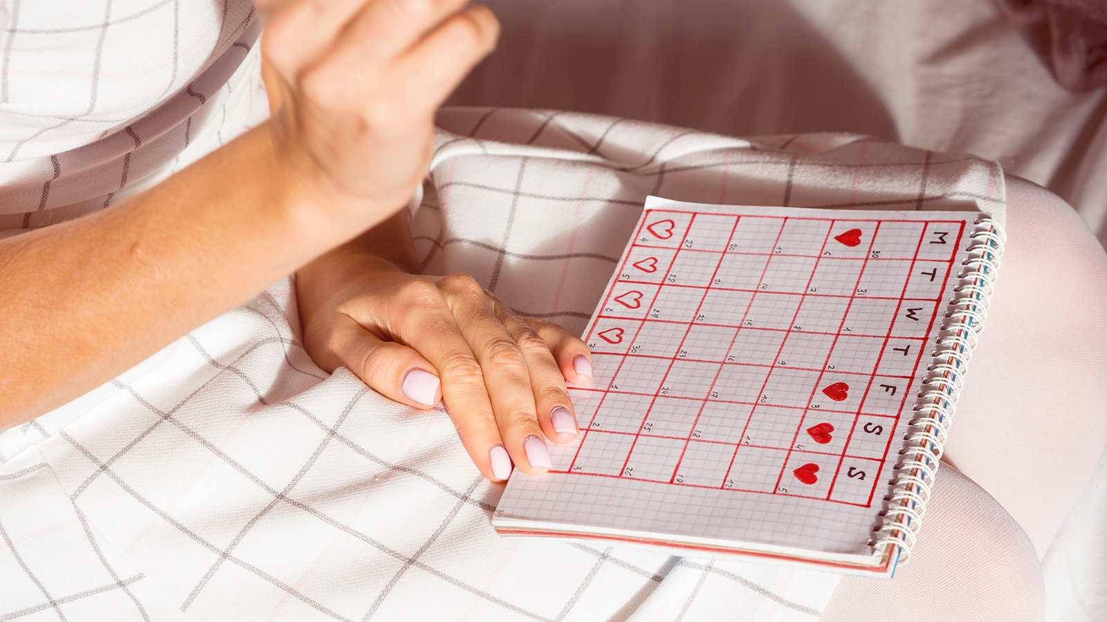 mulher usando um calendário para acompanhar sintomas da menstruação