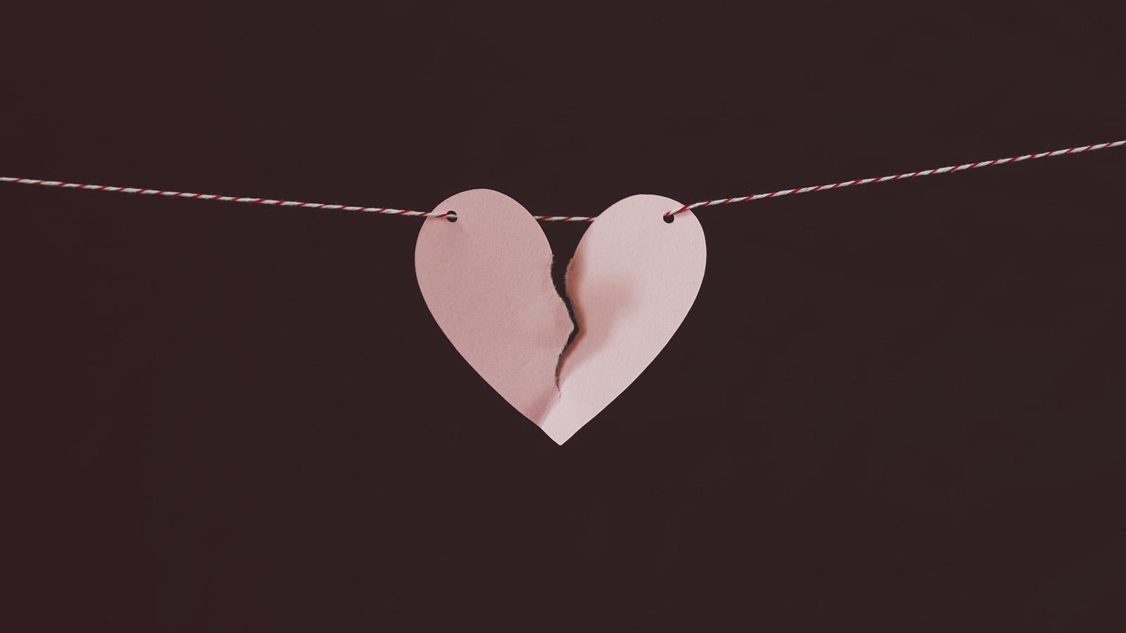 coração partido de papel em fundo preto