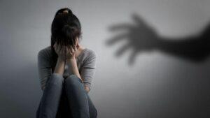 mulher chorando com a sombra de uma mão representando o que é assédio