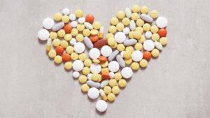 pilulas amontoadas em forma de coração representando o que corta o efeito do anticoncepcional