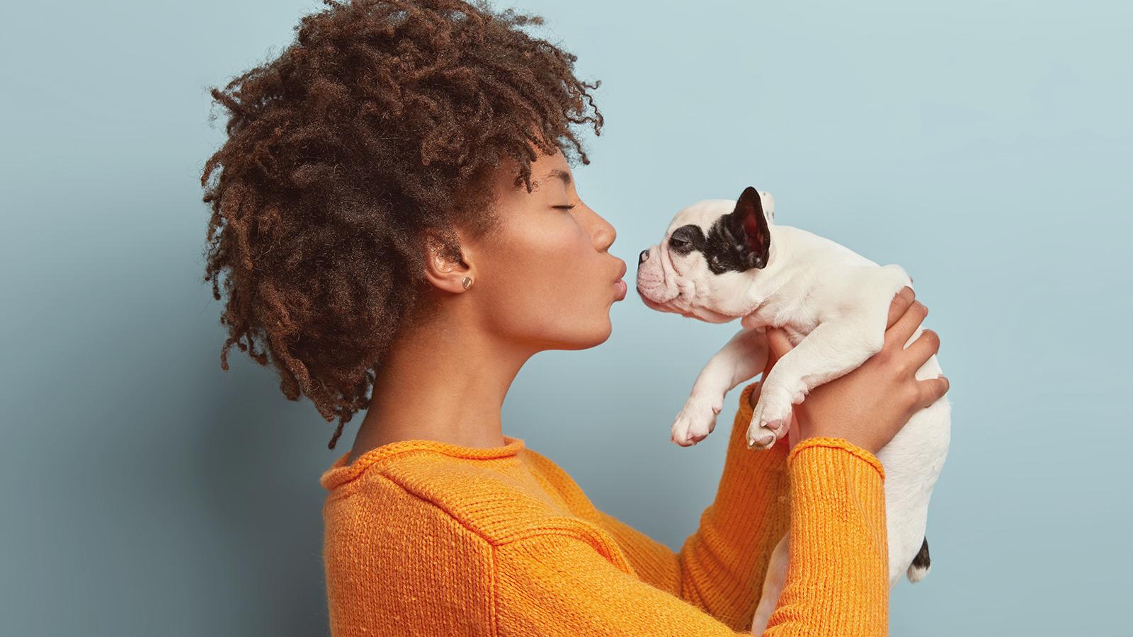 menina jovem simulando o primeiro beijo com um filhote de cachorro