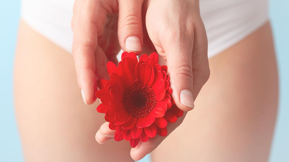 mulher segurando flor vermelha representando os tipos de hímen