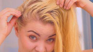 Mulher com o cabelo oleoso olhando a raiz do cabelo.