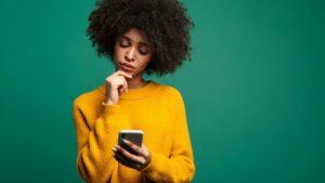 mulher olhando para o celular se perguntando como dar um fora