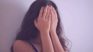 Menina com as mãos no rosto como quem diz: me sinto feia!