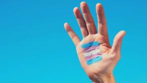 Mão erguida chamando atenção à saúde das pessoas trans