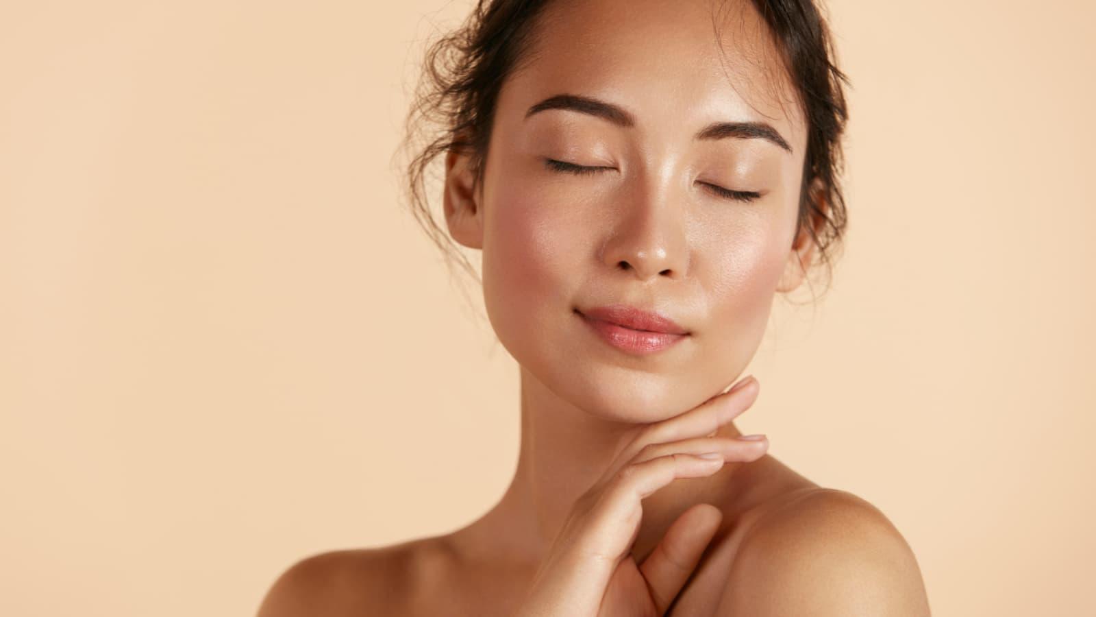 Mulher tocando o próprio rosto, demonstrando o cuidado necessário para cada tipo de pele